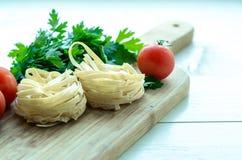 Ingredientes para cocinar las pastas italianas - espagueti, tomates, albahaca y ajo Fotografía de archivo