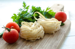 Ingredientes para cocinar las pastas italianas - espagueti, tomates, albahaca y ajo Imagen de archivo