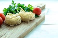 Ingredientes para cocinar las pastas italianas - espagueti, tomates, albahaca y ajo Imagen de archivo libre de regalías