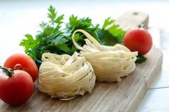 Ingredientes para cocinar las pastas italianas - espagueti, tomates, albahaca y ajo Foto de archivo