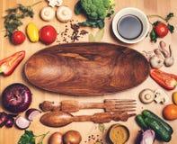 Ingredientes para cocinar Verduras alrededor de la placa de ensalada de madera Imágenes de archivo libres de regalías