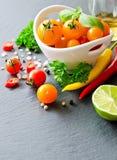 Ingredientes para cozinhar com os tomates de cereja amarelos, ervas, chil fotos de stock
