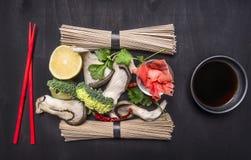 Ingredientes para cozinhar macarronetes japoneses crus do trigo mourisco no fim rústico de madeira da opinião superior do fundo a Imagem de Stock