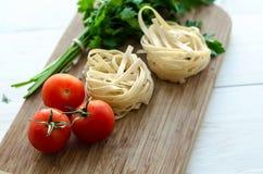 Ingredientes para cozinhar a massa italiana - espaguete, tomates, manjericão e alho Imagens de Stock Royalty Free