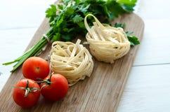 Ingredientes para cozinhar a massa italiana - espaguete, tomates, manjericão e alho Imagens de Stock