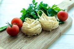 Ingredientes para cozinhar a massa italiana - espaguete, tomates, manjericão e alho Fotografia de Stock