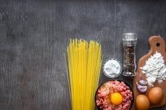 Ingredientes para cozinhar a massa Os espaguetes, ovos, azeite, alho, minsed a carne, a pimenta e o aipo fresco em de madeira Fotos de Stock Royalty Free