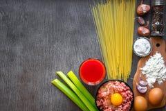 Ingredientes para cozinhar a massa Os espaguetes, suco de tomate, azeite, alho, minsed a carne, a pimenta e o aipo fresco sobre Fotografia de Stock
