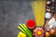 Ingredientes para cozinhar a massa Os espaguetes, suco de tomate, azeite, alho, minsed a carne, a pimenta e o aipo fresco sobre Fotos de Stock