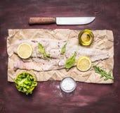 Ingredientes para cozinhar o bacalhau cru no fim de madeira rústico da opinião superior do fundo do óleo de sal da alface da rúcu fotografia de stock