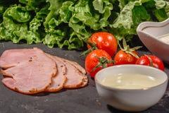 Ingredientes para cozinhar o bruschetta italiano na tabela escura Bruschetta italiano com tomates de cereja, molho de queijo, fol foto de stock royalty free