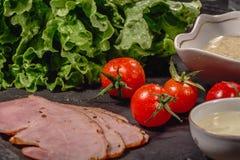Ingredientes para cozinhar o bruschetta italiano na tabela escura Bruschetta italiano com tomates de cereja, molho de queijo, fol fotografia de stock royalty free