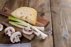 Ingredientes para cozinhar o jantar Cogumelos do queijo holandês e do cogumelo Cebolas verdes frescas Em uma placa e em um fundo  fotografia de stock royalty free