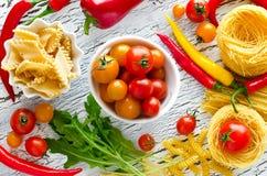 Ingredientes para cozinhar o verde amarelo vermelho da massa e dos vegetais imagem de stock royalty free