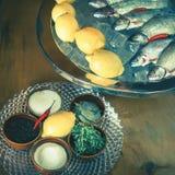 Ingredientes para cozinhar a truta, peixe do rio, com limão e especiarias Imagens de Stock Royalty Free