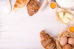 Ingredientes para croissant de cozimento - flour, colher de madeira, pino do rolo, ovos, gemas, manteiga servida no fundo branco Imagem de Stock Royalty Free