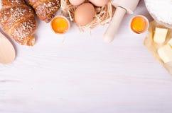 Ingredientes para croissant de cozimento - flour, colher de madeira, pino do rolo, ovos, gemas, manteiga servida no fundo branco Foto de Stock Royalty Free