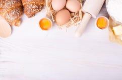 Ingredientes para croissant de cozimento - flour, colher de madeira, pino do rolo, ovos, gemas, manteiga servida no fundo branco Foto de Stock