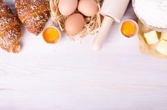 Ingredientes para croissant de cozimento - flour, colher de madeira, pino do rolo, ovos, gemas, manteiga servida no fundo branco Imagens de Stock Royalty Free