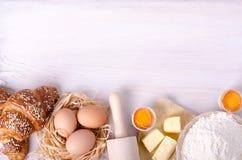 Ingredientes para croissant de cozimento - flour, colher de madeira, pino do rolo, ovos, gemas, manteiga servida no fundo branco Fotos de Stock