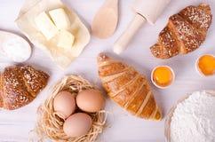 Ingredientes para croissant de cozimento - flour, colher de madeira, pino do rolo, ovos, gemas, manteiga servida no fundo branco Imagens de Stock