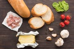 Ingredientes para el bocadillo con la carne ahumada, baguette en vagos de madera Imagen de archivo
