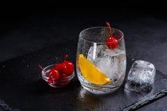 Ingredientes para el cóctel en un fondo negro de la pizarra Gass con el cubo de hielo, la rebanada anaranjada y la cereza con el  Fotografía de archivo