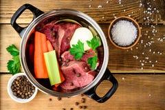 Ingredientes para el caldo de la carne en cacerola en la tabla de madera: carne de vaca, cebolla, zanahoria, apio, perejil y espe Fotografía de archivo libre de regalías