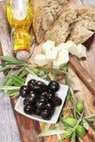 Ingredientes para el desayuno mediterráneo: pan fresco, queso feta, aceitunas y aceite adicional virginal En fondo de madera Fotos de archivo