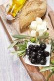 Ingredientes para el desayuno mediterráneo: pan fresco, queso feta, aceitunas y aceite adicional virginal En fondo de madera Foto de archivo