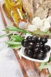 Ingredientes para el desayuno mediterráneo: pan fresco, queso feta, aceitunas y aceite adicional virginal En fondo de madera Fotografía de archivo libre de regalías