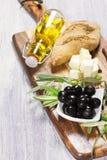 Ingredientes para el desayuno mediterráneo: pan fresco, queso feta, aceitunas y aceite adicional virginal En fondo de madera Imagenes de archivo