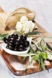 Ingredientes para el desayuno mediterráneo: pan fresco, queso feta, aceitunas y aceite adicional virginal En fondo de madera Fotografía de archivo