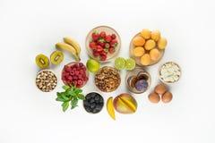 Ingredientes para el desayuno sano - bayas, fruta y nueces del desayuno del verano en el fondo blanco Imagen de archivo libre de regalías