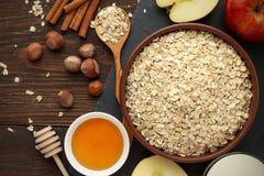 Ingredientes para el desayuno sano: la avena rodada forma escamas, ordeña, miel, avellana, canela en la tabla de madera rústica o Imagen de archivo
