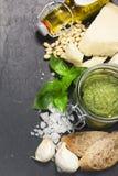 Ingredientes para el pesto: nueces de pino, albahaca, parmesano, aceite de oliva adicional virginal, ajo y sal Sobre piedra negra Fotografía de archivo libre de regalías