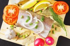 Ingredientes para el plato de pescados en tabla de cortar de madera Limón fresco de la rebanada, rábano colorido, ajo, guisantes  foto de archivo