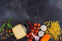 Ingredientes para el plato italiano Queso parmesano, pastas y verduras frescas En un viejo fondo de madera Imágenes de archivo libres de regalías