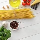 Ingredientes para el plato mediterráneo de las pastas: bucatini o espaguetis, tomates, albahaca, especia en el fondo de madera bl Foto de archivo libre de regalías