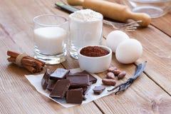Ingredientes para fazer cookies dos pedaços de chocolate em um fundo de madeira Foto de Stock