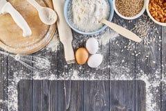Ingredientes para fazer a massa para o pão, pizza, bolo, biscoito na tabela de madeira cinzenta A vista da parte superior com lug Fotografia de Stock Royalty Free