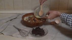 Ingredientes para fazer o chocolate do bolo Os queques do chocolate, amassam a massa Açúcar da farinha e chocolate amargo, ovo e  vídeos de arquivo