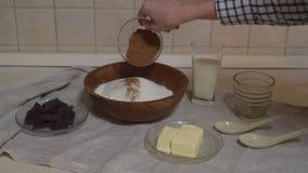 Ingredientes para fazer o chocolate do bolo Os queques do chocolate, amassam a massa Açúcar da farinha e chocolate amargo, ovo e  filme