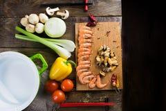 Ingredientes para fazer o marisco que encontra-se em uma tabela de madeira ao lado da bandeja vazia Fotos de Stock Royalty Free