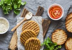 Ingredientes para hamburgueres do vegetariano - rissóis do grão-de-bico e da couve-flor, bolos, tomates, alface, molho em um fund Imagem de Stock Royalty Free