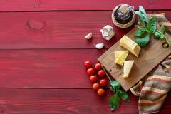Ingredientes para la cocina italiana Fondo de madera rojo imagenes de archivo