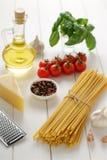 Ingredientes para la dieta mediterránea sana: bucatini de las pastas o con las verduras frescas, queso, aceite en la tabla de mad Foto de archivo