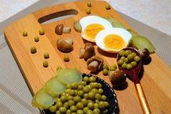 Ingredientes para la ensalada: pepinos conservados en vinagre, setas conservadas en vinagre, gre fotografía de archivo