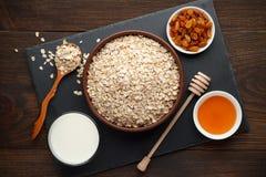 Ingredientes para la harina de avena en fondo de madera rústico: escamas, leche, miel y pasas de la avena rodada Foto de archivo libre de regalías