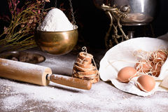 Ingredientes para la pasta y el pan, utensilio de cocinar: huevos marrones, harina, rodillo, cocinando el polvo Fotografía de archivo